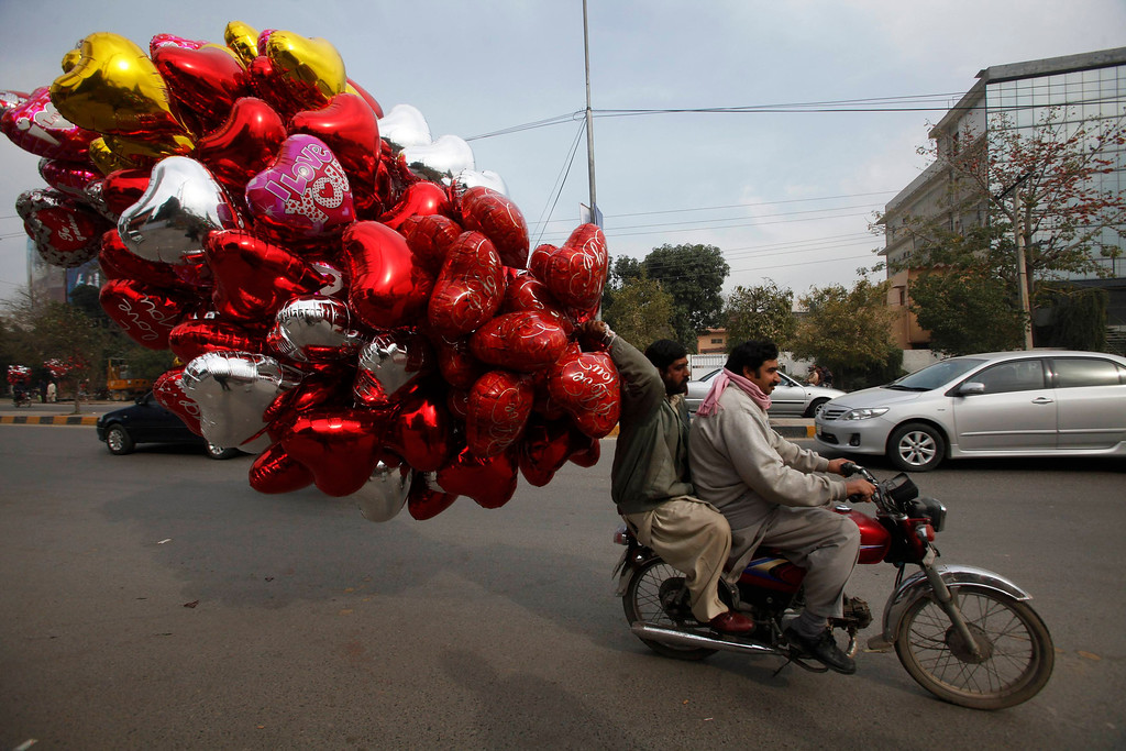 Description of . A man holds heart-shaped balloons while riding on a motorcycle along a road on Valentine's Day in Lahore February 14, 2013. REUTERS/Mohsin Raza