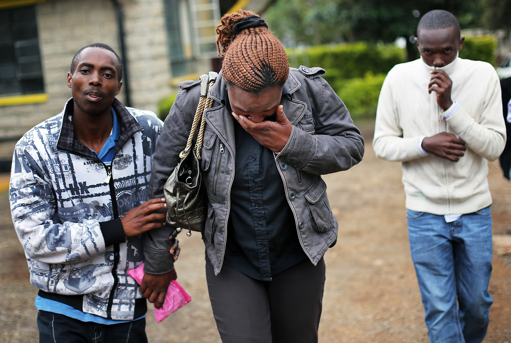 Description of . Zipporah Mureithi, 34, centre, is helped by relatives as she weeps after identifying the body of her father Paul, 56, at the city morgue in Nairobi, Kenya, Tuesday Sept. 24 2013.  Paul was one of the victims of the Westgate Mall hostage siege. Kenyan security forces are still combing the Mall on the fourth day of the siege by al-Qaida-linked terrorists. (AP Photo/ Jerome Delay)