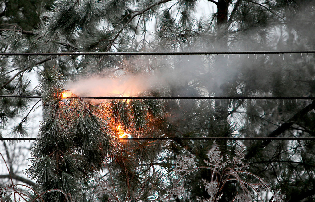 Description of . Ice-covered limbs falling on power lines cause a fire flair up along Main Street in Summerville, S.C., Wednesday, Feb. 12, 2014. A second winter storm in two weeks pummeled South Carolina on Wednesday, cutting power to tens of thousands and prompting Gov. Nikki Haley to ask President Barack Obama to declare the state a federal disaster area.   (AP Photo/The Post And Courier, Paul Zoeller)