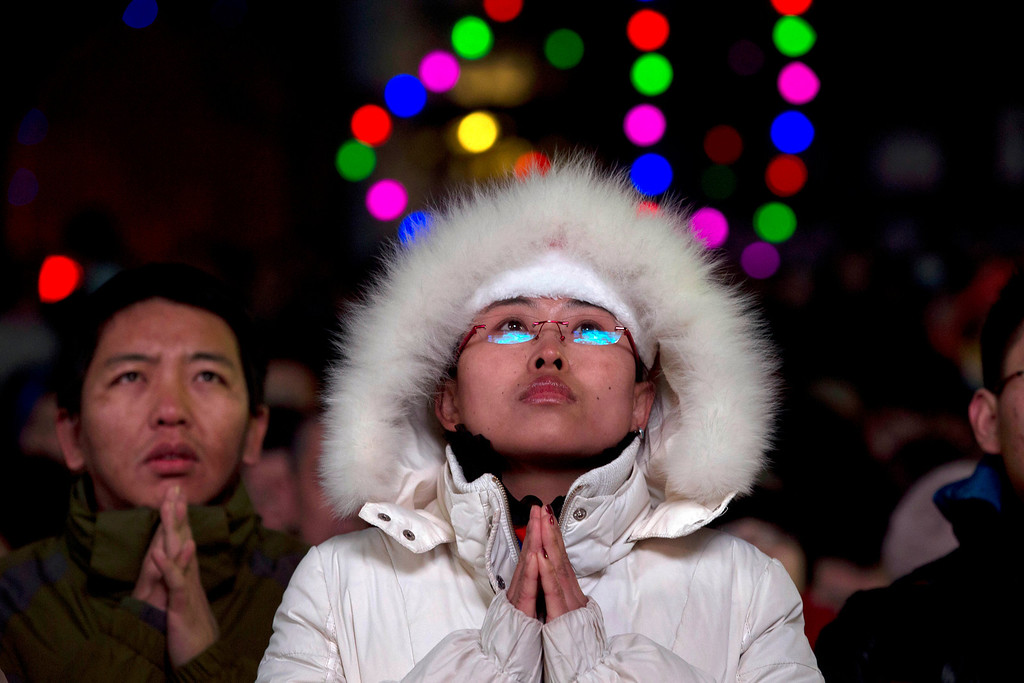 Description of . Chinese catholics attend a Christmas Eve Mass service at the official Catholic church South Cathedral in Beijing, China, Tuesday, Dec. 24, 2013.  China and the Vatican have no diplomatic ties and the ruling Communist Party forced Chinese Catholics to sever their ties in the 1950s. China officially records about 6 million Catholics worshipping in 6,300 congregations across the country, although millions more are believed to worship outside the official church, with considerable crossover between the two in many areas.  (AP Photo/Ng Han Guan)