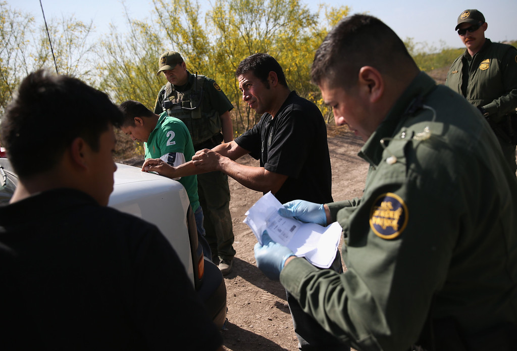 Description of . MISSION, TX - APRIL 11:  U.S. Border Patrol agents detain undocumented immigrants near the U.S.-Mexico border on April 11, 2013 near Mission, Texas. A group of 16 immigrants from Mexico and El Salvador said they crossed the Rio Grande River from Mexico into Texas during the morning hours before they were caught. The Rio Grande Valley sector of has seen more than a 50 percent increase in illegal immigrant crossings from last year, according to the Border Patrol. Agents say they have also seen an additional surge in immigrant traffic since immigration reform negotiations began this year in Washington D.C. Proposed refoms could provide a path to citizenship for many of the estimated 11 million undocumented workers living in the United States. Photo by John Moore/Getty Images)  (Photo by John Moore/Getty Images)