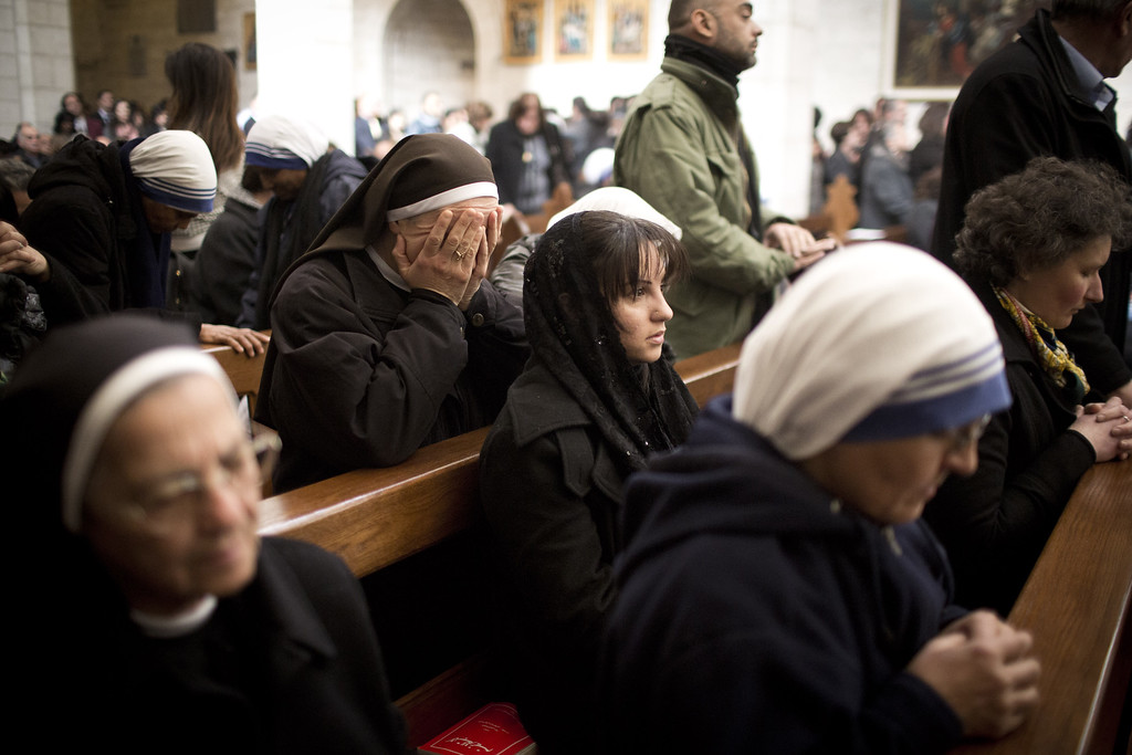 Description of . BETHLEHEM, WEST BANK - DECEMBER 25: Christian nuns pray during the Christmas mass at the Church of the Nativity on December 25, 2013 in Bethlehem, West Bank. Every Christmas pilgrims travel to the church where a gold star embedded in the floor marks the spot where Jesus was believed to have been born. (Photo by Oren Ziv/Getty Images)
