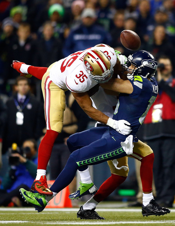 . Wide receiver Jermaine Kearse #15 of the Seattle Seahawks is hit by free safety Eric Reid #35 and strong safety Donte Whitner #31 of the San Francisco 49ers to break up the pass in the second half in the 2014 NFC Championship at CenturyLink Field on January 19, 2014 in Seattle, Washington.  (Photo by Jonathan Ferrey/Getty Images)