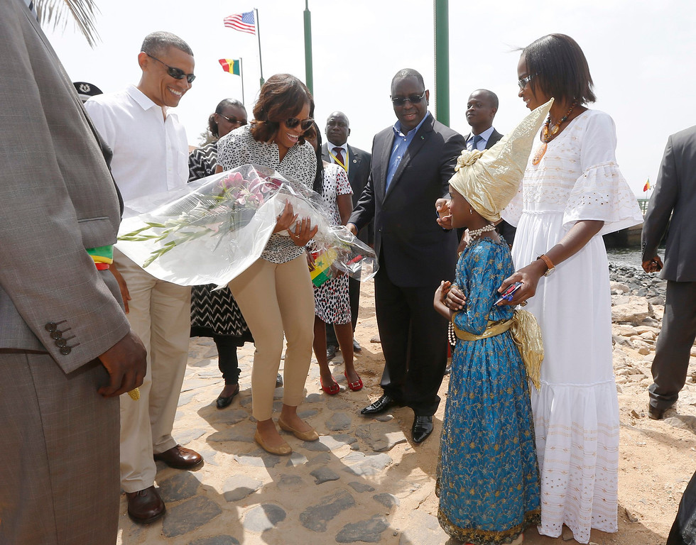Description of . U.S. President Barack Obama and first lady Michelle Obama receive a bouquet as they arrive on Goree Island near Dakar, Senegal, June 27, 2013.  Obama visited the island on Thursday where African slaves in past centuries were shipped west. REUTERS/Jason Reed