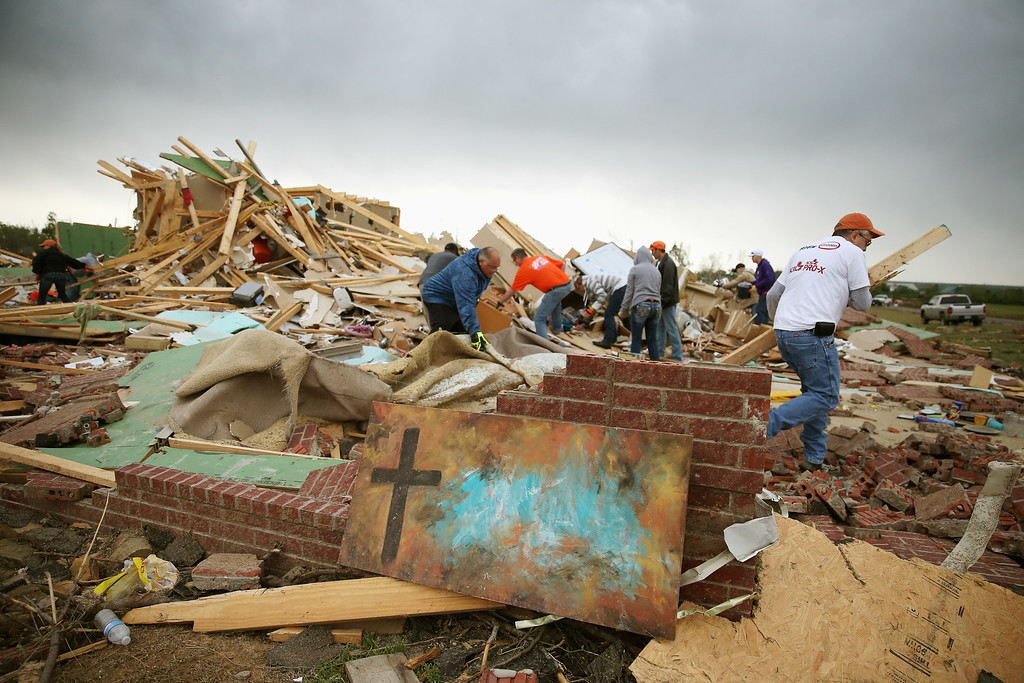 Description of . Volunteers help clean debris at the site of a home that was detroyed after a tornado hit the area April 29, 2014 in Vilonia, Arkansas.  (Photo by Mark Wilson/Getty Images)