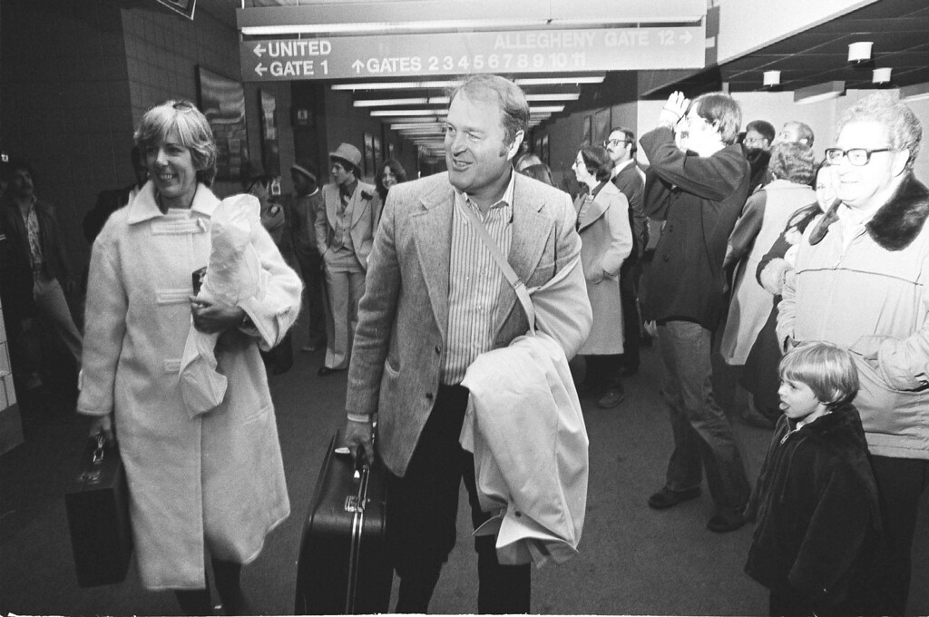 . Pittsburgh Steelers head coach Chuck Noll,center, with his broken left elbow  in a sling, arrives at Pittsburgh airport after his team clinched a playoff  Sunday, Dec. 19, 1977. (AP Photo)