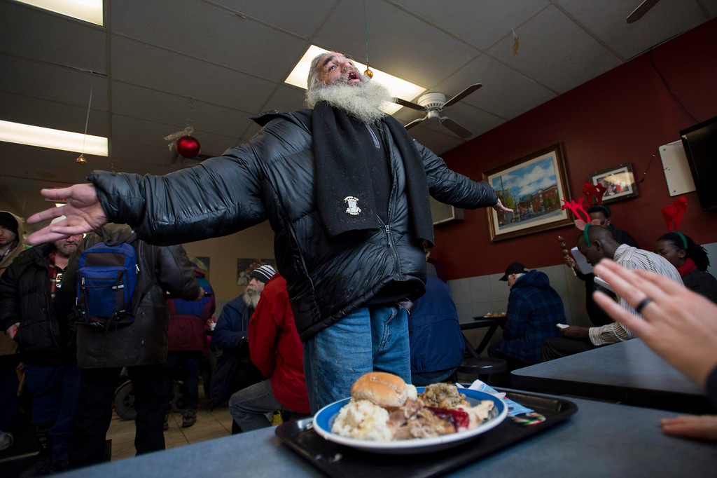 Description of . Moses Gibson dances to choir songs after receiving his Christmas day lunch at the Shepherds of Good Hope in Ottawa, Ontario on Wednesday, Dec. 25, 2013. (AP Photo/The Canadian Press, Justin Tang)