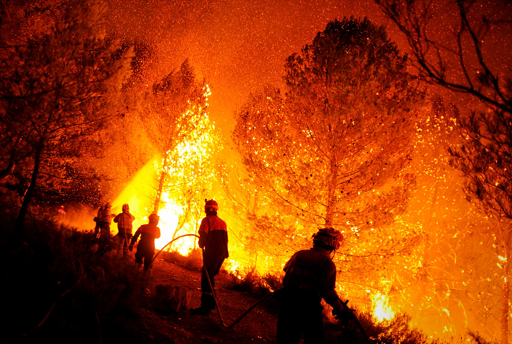 Description of . A firefighter of Alcoy and Elda try to extinguish a fire in Torre de Macanes near Alicante, on August 13, 2012. One person was killed and three injured Sunday as firefighters battled wildfires across Spain, authorities said, the latest victims in a sweltering summer of forest blazes. (PEDRO ARMESTRE/AFP/GettyImages)