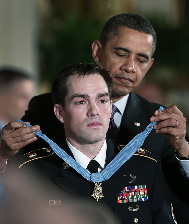 Description of . U.S. President Barack Obama (R) presents the Medal of Honor for conspicuous gallantry to Clinton Romesha (L), a former active duty Army Staff Sergeant, at the White House February 11, 2013 in Washington, DC (Photo by Win McNamee/Getty Images)