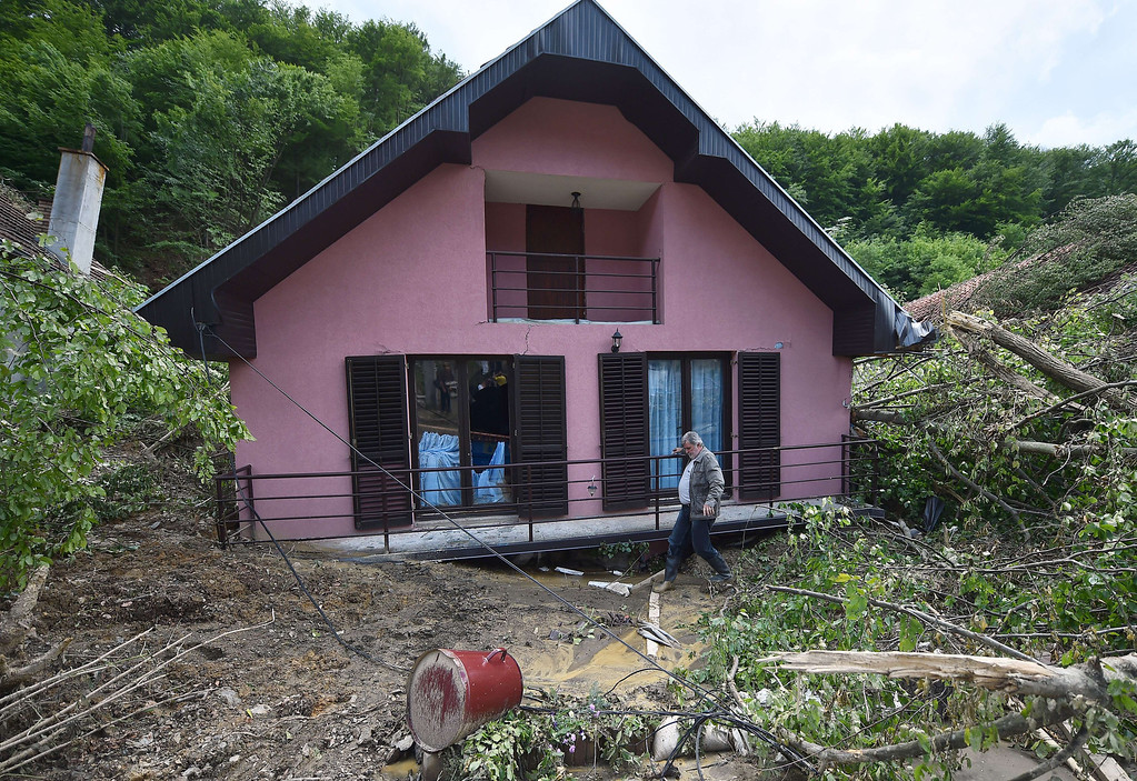 Description of . A man walks past a house damaged by flooding and landslide  in Krupanj, some 130 kilometers south west of Belgrade, on May 20, 2014, after the western Serbian town was hit with floods and landslides, cutting it off for four days. Serbia declared three days of national mourning on May 20 as the death toll from the worst flood to hit the Balkans in living memory rose and health officials warned of a possible epidemic.   AFP PHOTO / ANDREJ  ISAKOVIC/AFP/Getty Images