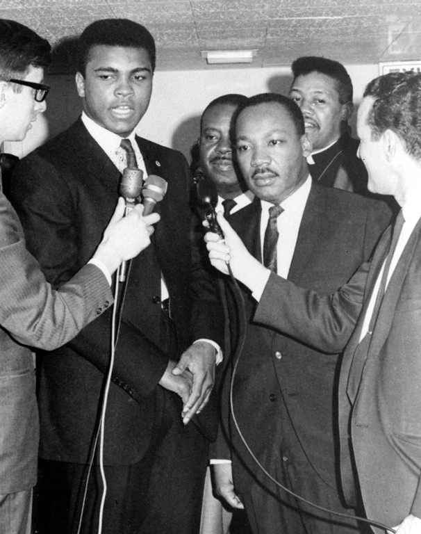 Description of . Heavyweight champion Muhammad Ali, left center, talks to the media in Louisville, Ky., after conferring with civil rights activist Dr. Martin Luther King, right center, regarding the boxer's draft status in this March 29, 1967 file photo. Ali was in his hometown for his court suit to prevent his Army induction April 28 in Houston. Later, the NAACP Legal Defense Fund represented Ali when the high court struck down his conviction for refusing to serve in the military. (AP Photo)