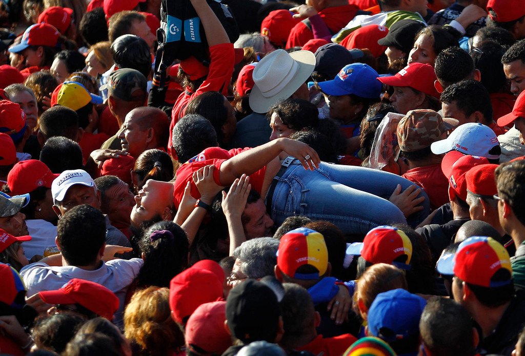 Description of . A supporter of Venezuela's late President Hugo Chavez is lifted out of the crowd after fainting while waiting for a chance to view his body at the military academy in Caracas March 8, 2013. Chavez will be embalmed and put on display