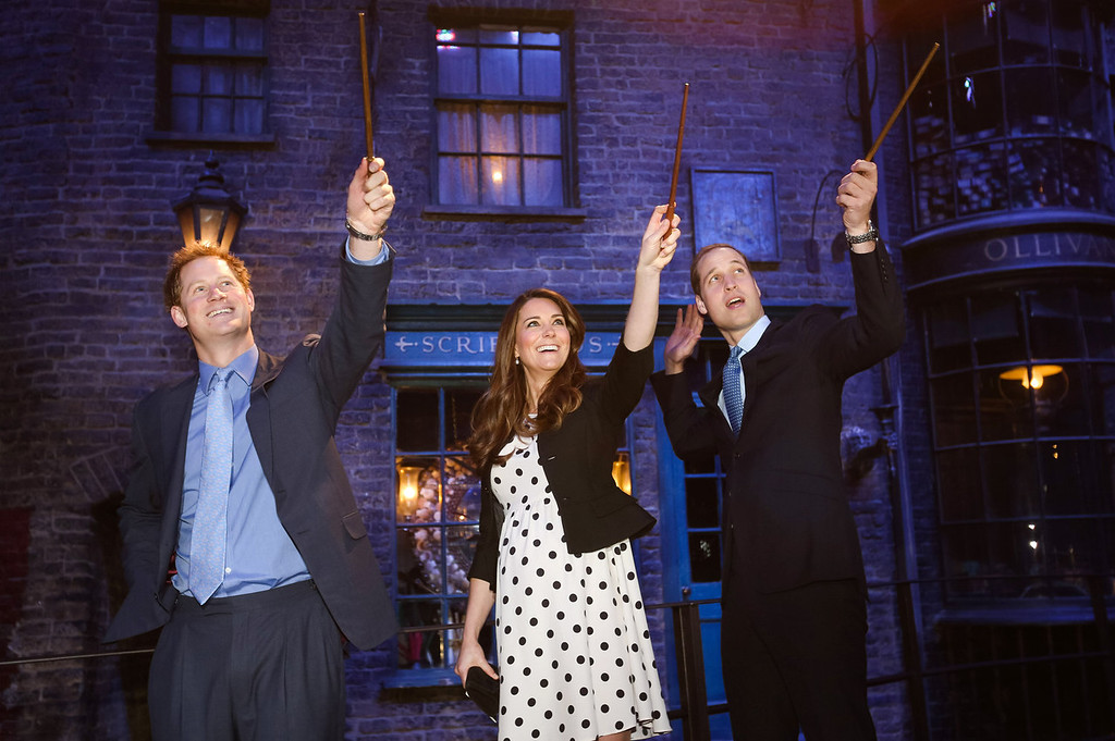 Description of . Prince Harry, Catherine, Duchess of Cambridge and Prince William, Duke of Cambridge raise their wands on the set used to depict Diagon Alley in the Harry Potter Films during the Inauguration Of Warner Bros. Studios Leavesden on April 26, 2013 in London, England.  (Photo by Paul Rogers - WPA Pool/Getty Images)