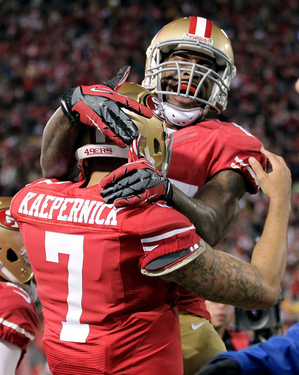 . San Francisco 49ers quarterback Colin Kaepernick (7) celebrates after running for touchdown with tight end Vernon Davis during the first quarter of an NFC divisional playoff NFL football game against the Green Bay Packers in San Francisco, Saturday, Jan. 12, 2013. (AP Photo/Tony Avelar)
