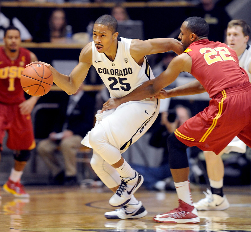 Description of . Spencer Dinwiddie of Colorado is held up by Byron Wesley of Southern California during the first half of the January 10, 2013 game in Boulder.   Cliff Grassmick/Daily Camera