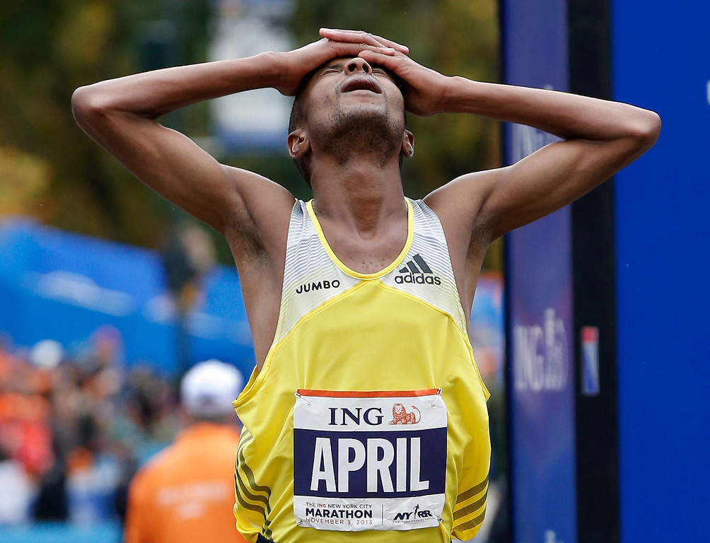 Description of . Third-placed Lusapho April, of South Africa, reacts after finishing the New York City Marathon, Sunday, Nov. 3, 2013, in New York. (AP Photo/Kathy Willens)