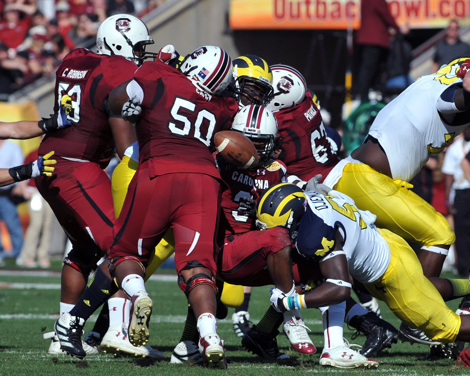 Description of . Running back Kenny Miles #31 of the South Carolina Gamecocks fumbles in the second quarter  against the Michigan Wolverines in the Outback Bowl January 1, 2013 at Raymond James Stadium in Tampa, Florida.  (Photo by Al Messerschmidt/Getty Images)