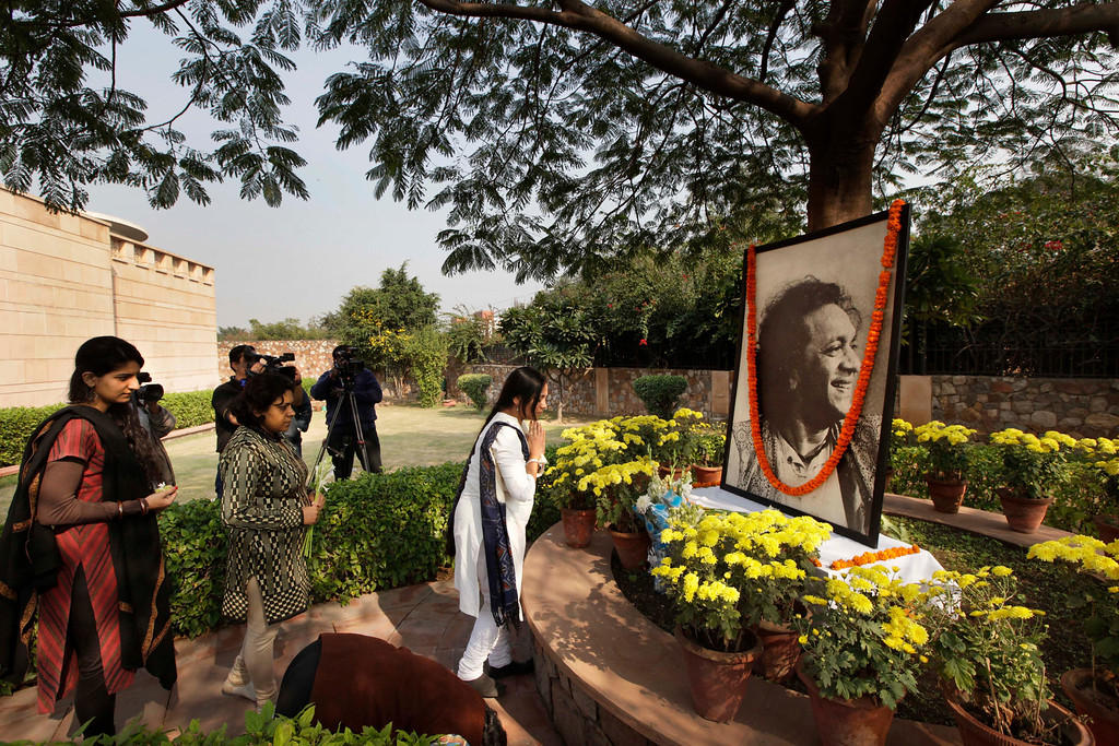 . Indians pay their respects next to a portrait of legendary Indian sitar player Ravi Shankar placed under a tree as part of a makeshift memorial at his music center, in New Delhi, India, Wednesday, Dec. 12, 2012. Shankar, who is credited with connecting the world to Indian music, died Tuesday in San Diego at the age of 92. (AP Photo/ Manish Swarup)