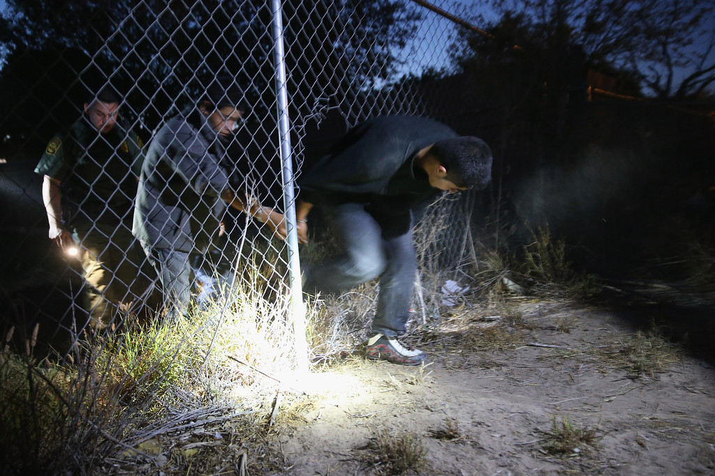 Description of . MISSION, TX - APRIL 11:  A U.S. Border Patrol agent detains undocumented immigrants who had crossed from Mexico into the United States on April 11, 2013 in Mission, Texas. In the last month the Border Patrol\'s Rio Grande Valley sector has seen a spike in the number of immigrants crossing the river from Mexico into Texas. With more apprehensions, they have struggled to deal with overcrowding while undocumented immigrants are processed for deportation. According to the Border Patrol, undocumented immigrant crossings have increased more than 50 percent in Texas\' Rio Grande Valley sector in the last year. Border Patrol agents say they have also seen an additional surge in immigrant traffic since immigration reform negotiations began this year in Washington D.C. Proposed reforms could provide a path to citizenship for many of the estimated 11 million undocumented workers living in the United States.  (Photo by John Moore/Getty Images)