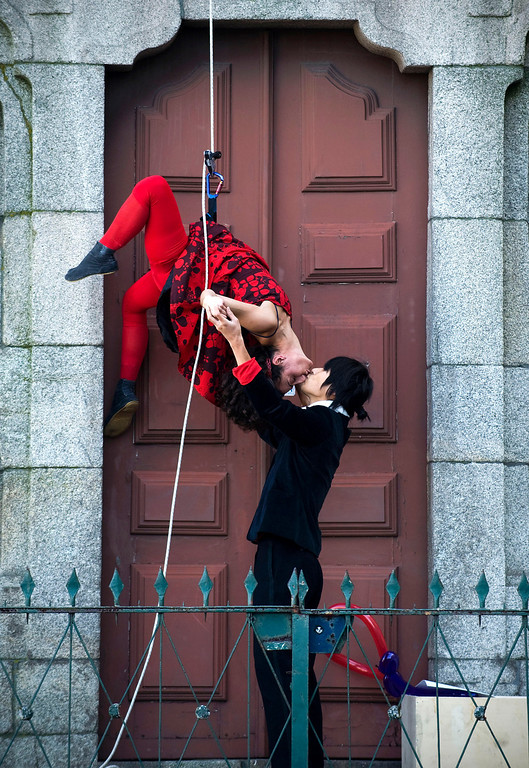 Description of . Portuguese performer Pauliana Almeida, 34, kisses her fiancee Japan's Yuga Hatta, 26, after rappelling down the Clerigos' Tower during a performance to mark St. Valentine's Day, Porto, Portugal, Thursday, Feb. 14, 2013. (AP Photo/Paulo Duarte)