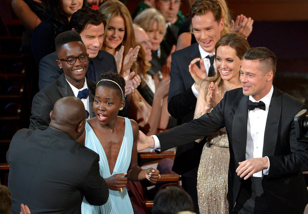 Description of . Director Steve McQueen, left, congratulates Lupita Nyong'o on her win for best actress in a supporting role for