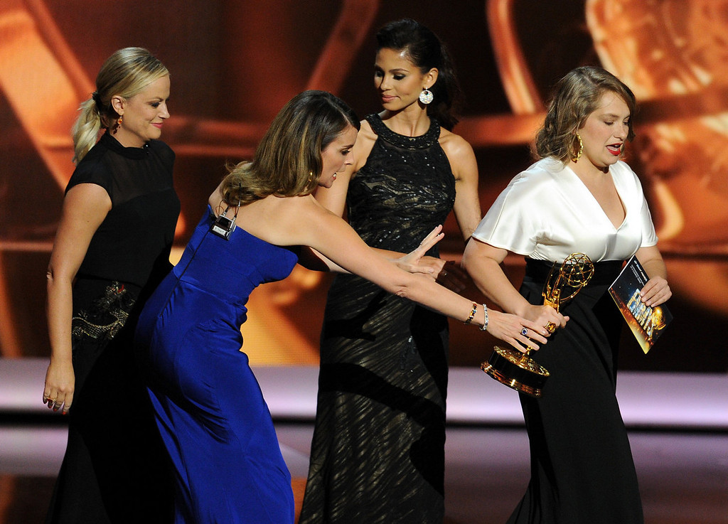 Description of . (L-R) Actress/writers Amy Poehler and Tina Fey, and Winner for Supporting Actress in a Comedy Series Merritt Wever speak onstage during the 65th Annual Primetime Emmy Awards held at Nokia Theatre L.A. Live on September 22, 2013 in Los Angeles, California.  (Photo by Kevin Winter/Getty Images)