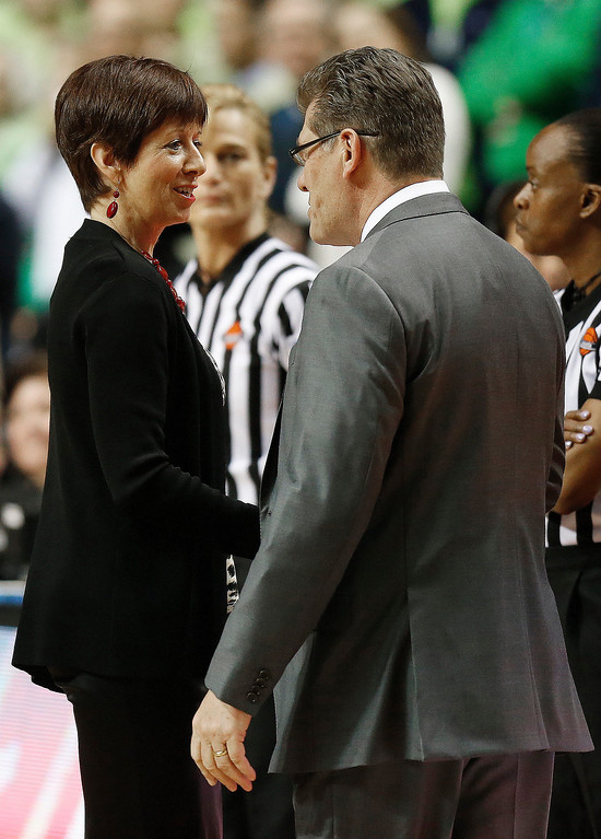 Description of . Notre Dame head coach Muffet McGraw, left, greets Connecticut head coach Geno Auriemma before the first half of the championship game in the Final Four of the NCAA women's college basketball tournament, Tuesday, April 8, 2014, in Nashville, Tenn. (AP Photo/John Bazemore)