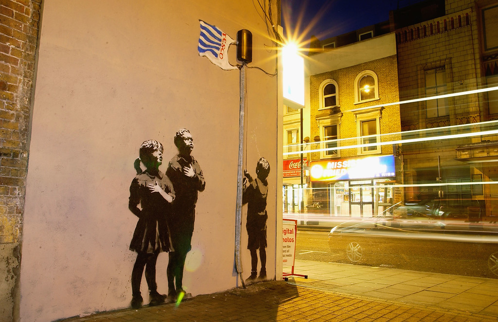 Description of . Artwork in North London, attributed to guerrilla graffiti artist Banksy, is pictured on Essex Road in Islington on March 4, 2008 in London, England. The scene depicts children gathering around a flagpole topped by a Tesco carrier bag. (Photo by Jim Dyson/Getty Images)