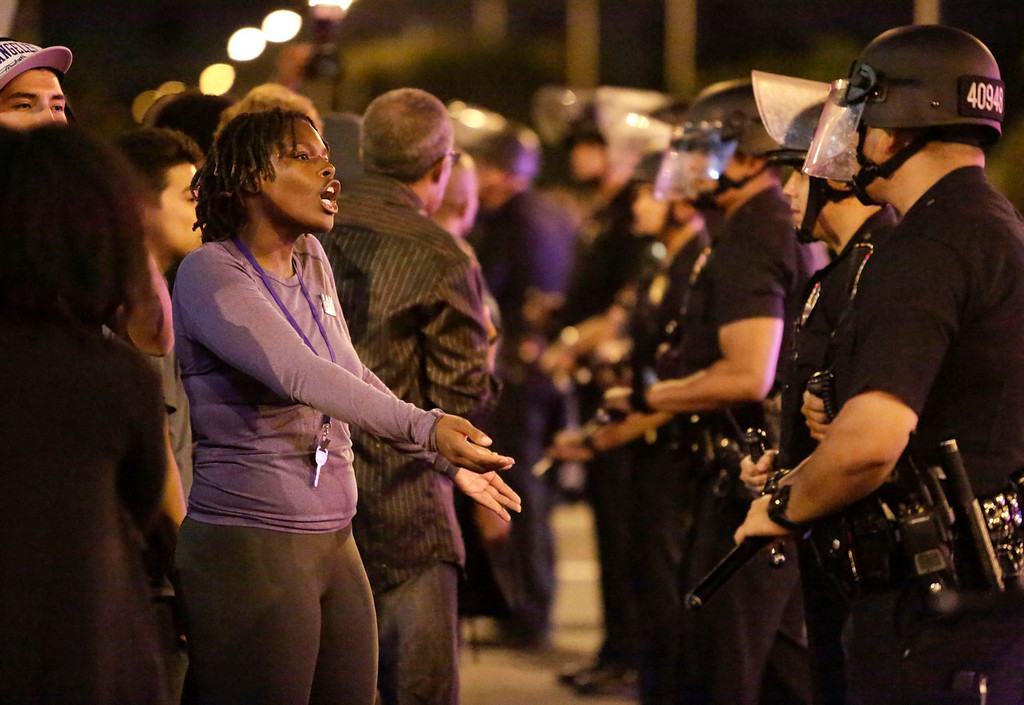 Description of . A protester (L) talks with Los Angeles Police officers as they try to remove protesters from the intersection of Exposition and Crenshaw boulevards, following the George Zimmerman verdict in Los Angeles, California, July 13, 2013. A Florida jury acquitted Zimmerman on Saturday for the shooting death of unarmed black teenager Trayvon Martin, setting free a man who had become a polarizing figure in the national debate over racial profiling and self-defense laws. REUTERS/Jason Redmond