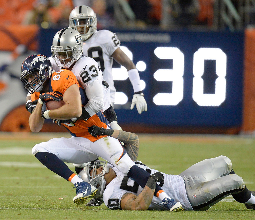 Description of . Denver Broncos tight end Jacob Tamme (84) is tackled by Oakland Raiders outside linebacker Kaluka Maiava (50) and Oakland Raiders cornerback Tracy Porter (23) in the third quarter. The Denver Broncos took on the Oakland Raiders at Sports Authority Field at Mile High in Denver on September 23, 2013. (Photo by John Leyba/The Denver Post)
