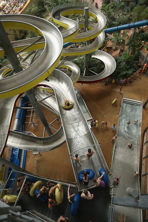 Description of . Visitors ride inner tubes down that water slide at the Tropical Islands indoor resort on February 15, 2013 in Krausnick, Germany. Located on the site of a former Soviet military air base, the resort occupies a hangar built originally to house airships designed to haul long-distance cargo. Tropical Islands opened to the public in 2004 and offers visitors a tropical getaway complete with exotic flora and fauna, a beach, lagoon, restaurants, water slide, evening shows, sauna, adventure park and overnights stays ranging from rudimentary to luxury. The hangar, which is 360 metres long, 210 metres wide and 107 metres high, is tall enough to enclose the Statue of Liberty.  (Photo by Sean Gallup/Getty Images)