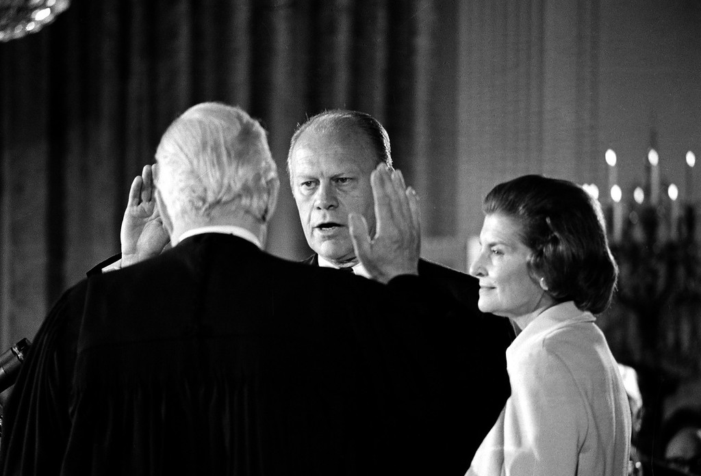 Description of . Gerald R. Ford takes the oath of office as the 38th President of the United States as his wife, Betty, right, stands at his side in the East Room of the White House in Washington, D.C., Friday, Aug. 4. 1974.  Administering the oath is Chief Justice of the United States Warren Burger. Ford was sworn in following the resignation of Richard M. Nixon as chief executive. (AP Photo)