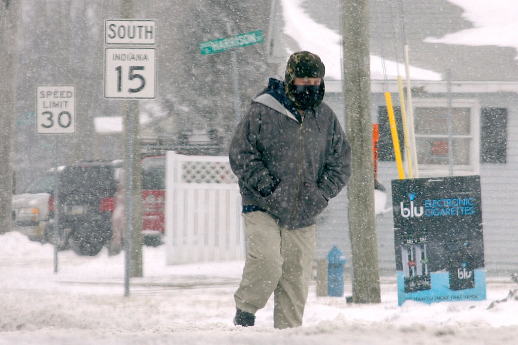 Description of . Bundled against the cold, a pedestrian crosses South Western Avenue in Marion, Ind., on Thursday, Jan. 2, 2014. Most of Indiana was under a winter weather advisory Thursday from the National Weather Service.  (AP Photo/The Chronicle-Tribune, Jeff Morehead)