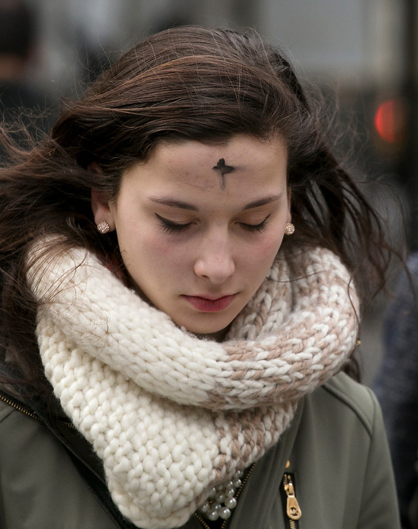 Description of . A woman leaves an Ash Wednesday service at St. Patrick's Cathedral, Wednesday, March 5, 2014 in New York. Some Protestant, and all Catholic churches, distribute ashes on the forehead as a sign of repentance and renewal on Ash Wednesday as the 40-day season leading to Easter begins. (AP Photo/Mark Lennihan)