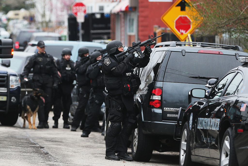 Description of . A Boston SWAT team member takes up as posistion as they search for 19-year-old bombing suspect Dzhokhar A. Tsarnaev on April 19, 2013 in Watertown, Massachusetts.  (Photo by Mario Tama/Getty Images)