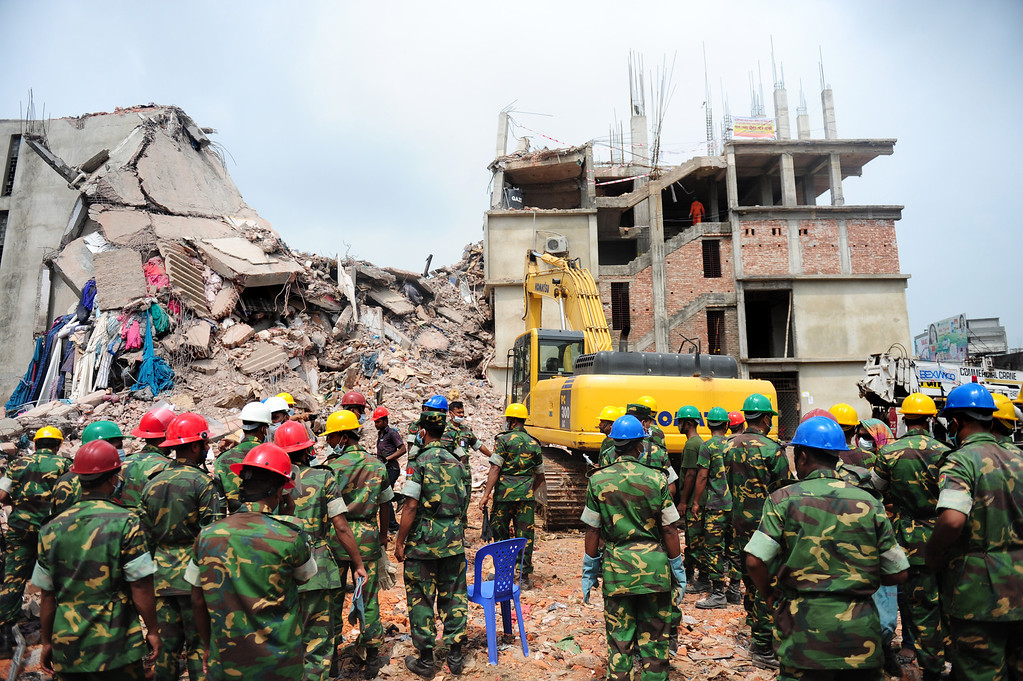 Description of . Bangladeshi rescuers work as Bangladeshi Army personnel continue the second phase of the rescue operation using heavy equipment after an eight-story building collapsed in Savar, on the outskirts of Dhaka, on April 30, 2013. AFP PHOTO/MUNIR UZ ZAMAN/AFP/Getty Images