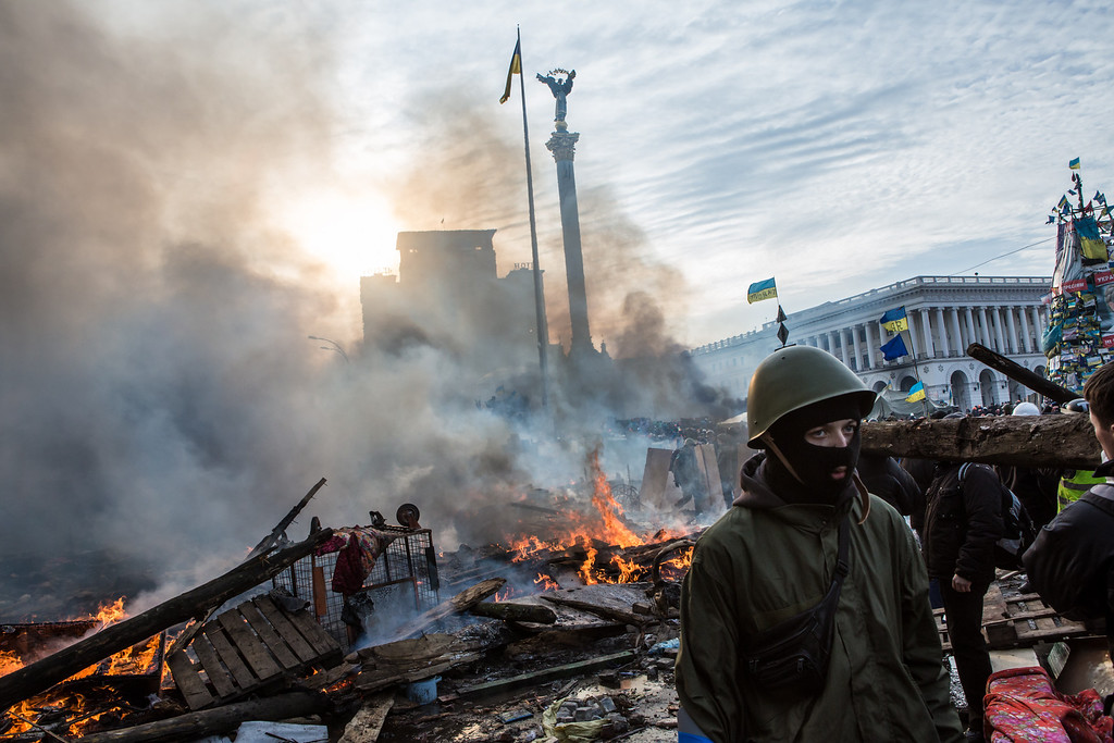 Description of . Anti-government protesters walk amid debris and flames near the perimeter of Independence Square, known as Maidan, on February 19, 2014 in Kiev, Ukraine. (Photo by Brendan Hoffman/Getty Images)
