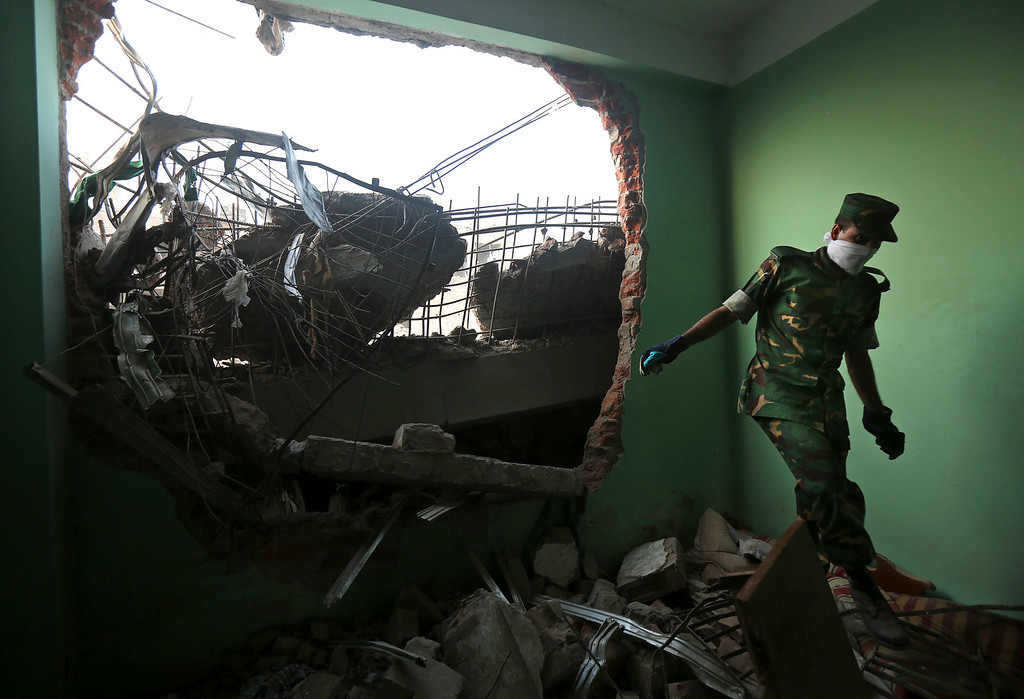 Description of . A Bangladeshi army soldier walks in the rubble at the site of a building that collapsed Wednesday in Savar, near Dhaka, Bangladesh, Thursday, April 25, 2013. (AP Photo/Kevin Frayer)