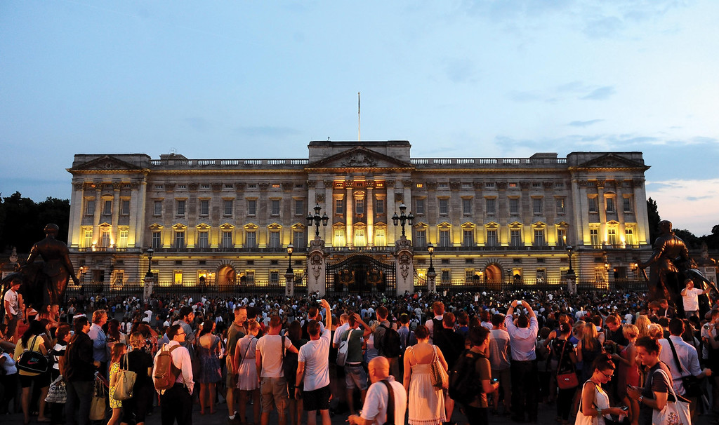 Description of . Members of the public celebrate outside Buckingham Palace after an easel was placed in the forecourt of the Palace with the notification to announce the birth of a baby boy, at 4.24pm to the Duke and Duchess of Cambridge at St Mary\'s Hospital in west London, Monday July 22, 2013.(AP Photo/Clive Gee, PA)