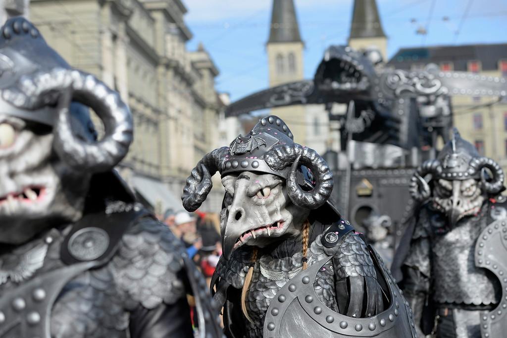 Description of . Masked revelers tour through the streets during the start of the carnival season in Lucerne, Switzerland, Thursday, Feb. 27, 2014. (AP Photo/Keystone, Urs Flueeler)