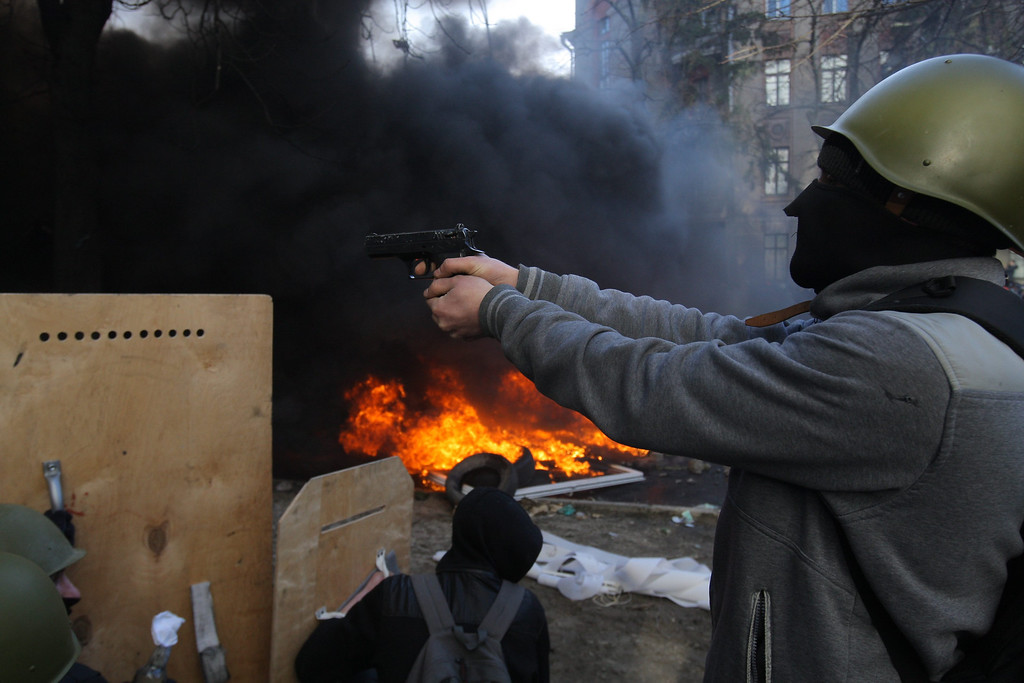 Description of . A protester aims a gun to riot police during continuing protests in downtown Kiev, Ukraine, 18 February 2014.  EPA/OLEG PETRASYUK