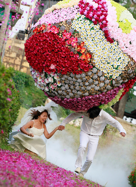 Description of . Chutuma Tapoatong, left, and Sopon Tapoatong try to run away from a giant flower ball as a part of an adventure-themed wedding ceremony in Prachinburi province, Thailand, Wednesday, Feb. 13, 2013, on the eve of Valentine's Day. Three couples participated in the ceremony. (AP Photo/Wason Wanichakorn)