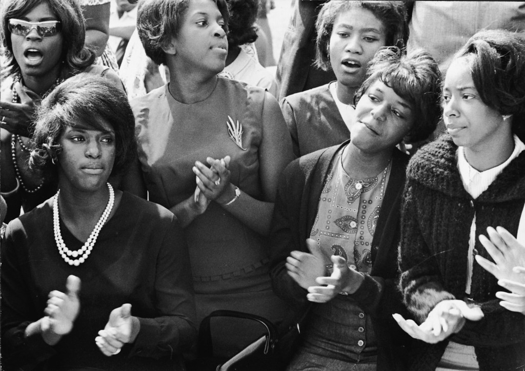 Description of . To pass the long morning, young women clap and sing along to a freedom song between speeches at the March on Washington for Jobs and Freedom, Washington DC, August 28, 1963. (Photo by Express Newspapers/L360/Getty Images)