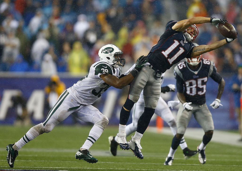 Description of . Julian Edelman #11 of the New England Patriots catches a pass in front of Antonio Allen #39 of the New York Jets in the fourth quarter during the game at Gillette Stadium on September 12, 2013 in Foxboro, Massachusetts. (Photo by Jared Wickerham/Getty Images)