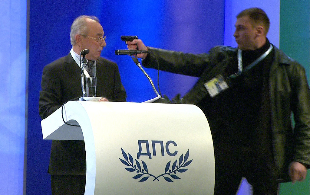 Description of . This video grab broadcast by Bulgarian television channel BTV shows a man (R) pointing a pistol at leader of the Turkish minority Movement for Rights and Freedoms (MRF) party Ahmed Dogan during his speech at a national party conference in Sofia on January 19, 2013. Dogan was addressing the delegates at the conference when the man rushed up to the podium and put a pistol to his head. The attacker however failed to produce a shot and was quickly disarmed by the delegates, witnesses told state BNR radio.   AFP/Getty Images