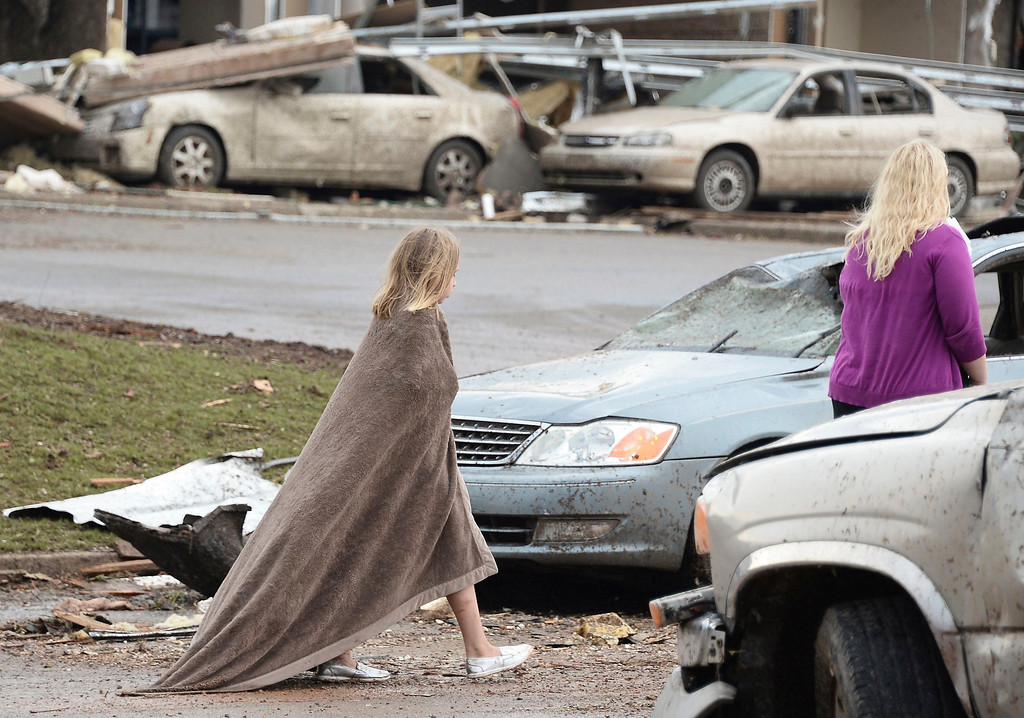 . A girl tries to keep warm near the Moore Hospital after being hit tornado that destroyed buildings and overturned cars in Moore, Oklahoma, May 20, 2013.  A huge tornado with winds of up to 200 miles per hour (320 kph) devastated the Oklahoma City suburb of Moore on Monday, ripping up at least two elementary schools and a hospital and leaving a wake of tangled wreckage. REUTERS/Gene Blevins