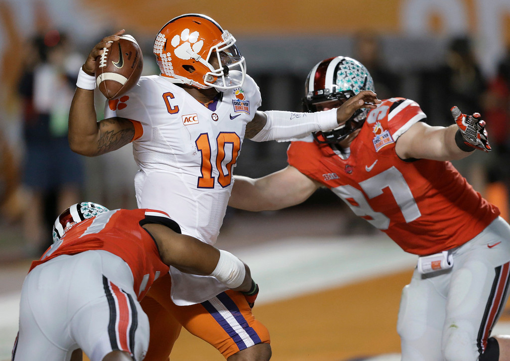 Description of . Clemson quarterback Tajh Boyd (10) looks to pass as he is pressured by Ohio State linebacker Joshua Perry, left, and defensive lineman Joey Bosa (97) during the first half of the Orange Bowl NCAA college football game, Friday, Jan. 3, 2014, in Miami Gardens, Fla. (AP Photo/Wilfredo Lee)