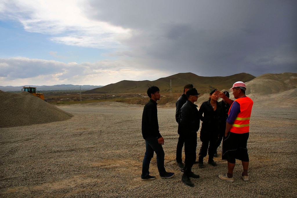 Description of . Members of the Mongolian neo-Nazi group Tsagaan Khass talk to a worker at a quarry southwest of Ulan Bator June 23, 2013. The group has rebranded itself as an environmentalist organisation fighting pollution by foreign-owned mines, seeking legitimacy as it sends Swastika-wearing members to check mining permits.Over the past years, ultra-nationalist groups have expanded in the country and among those garnering attention is Tsagaan Khass, which has recently shifted its focus from activities such as attacks on women it accuses of consorting with foreign men to environmental issues, with the stated goal of protecting Mongolia from foreign mining interests. This ultra-nationalist group was founded in the 1990s and currently has 100-plus members. Picture taken June 23, 2013. REUTERS/Carlos Barria