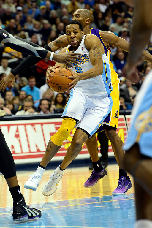 Description of . Denver Nuggets shooting guard Andre Iguodala (9) drives past Los Angeles Lakers shooting guard Kobe Bryant (24) during the first half at the Pepsi Center on Wednesday, December 26, 2012. AAron Ontiveroz, The Denver Post