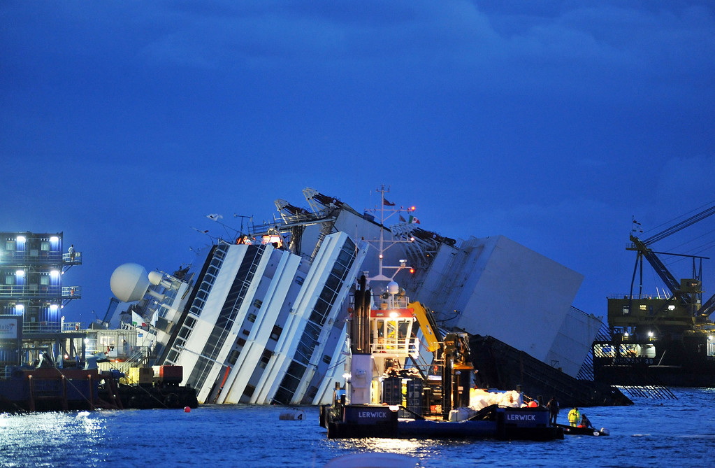 Description of . Titan and Micoperi workers are seen next to the stricken Costa Concordia on September 16, 2013 in Isola del Giglio, Italy. Work begins today to right the stricken Costa Concordia vessel, which sank on January 12, 2012. If the operation is successful, it will then be towed away and scrapped. The procedure, known as parbuckling, has never been carried out on a vessel as large as Costa Concordia before. (Photo by Laura Lezza/Getty Images)